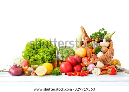 Different fresh vegetables and fruits in basket on wooden table isolated on a white background. - stock photo