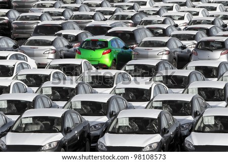 Different from others - Lonely green car among set of others white used as a background - stock photo