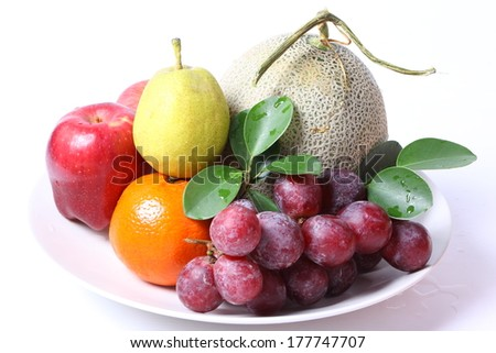 Different fruits on white plate - stock photo
