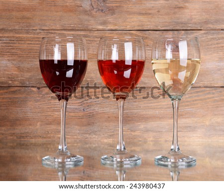 Different glasses of wine on table on wooden background - stock photo