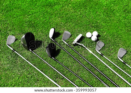 Different golf clubs in a row and balls on a green grass - stock photo