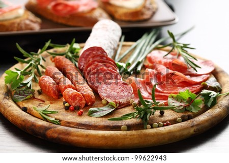 Different Italian ham and salami with herbs - stock photo