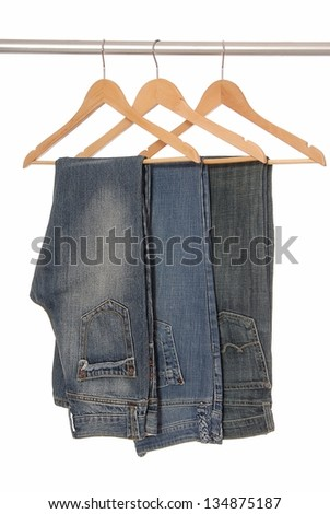 Different  jeans are on woody hangers. - stock photo