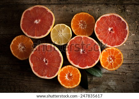 Different kind of citrus fruits on wooden board - stock photo