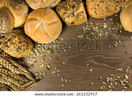 Different kind of freshly baked bread rolls on wooden table - stock photo
