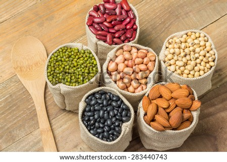 Different kinds of beans in sacks bag on wooden background - stock photo