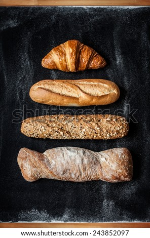 Different kinds of bread rolls on black chalkboard from above. Kitchen or bakery poster design. - stock photo