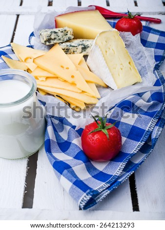Different kinds of cheese on blue napkin on a light wooden background - stock photo