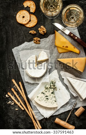 Different kinds of cheeses, white wine and snacks on black chalkboard background captured from above (top view). French tasting party or feast scenery. - stock photo