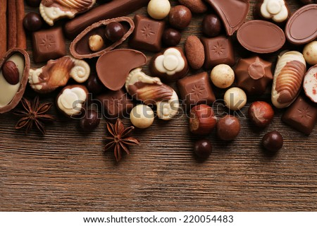 Different kinds of chocolates on wooden table close-up - stock photo