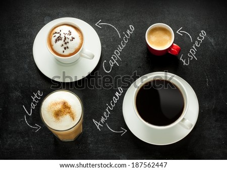 Different kinds of coffee on black chalkboard background. Cappuccino, espresso, americano and latte from above - cafe menu or poster. - stock photo