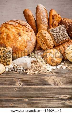 Different kinds of fresh bread on wooden table - stock photo