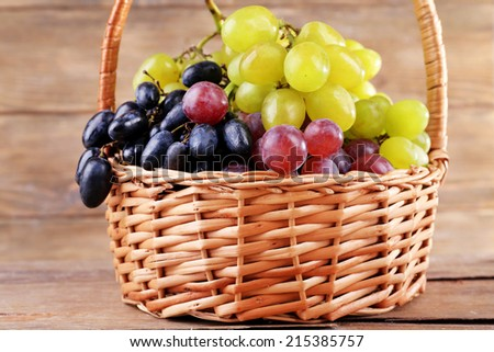 Different kinds of grapes in wicker basket on wooden background - stock photo
