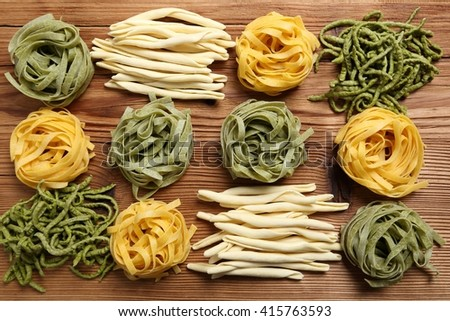 Different kinds of pasta on the wooden background. - stock photo
