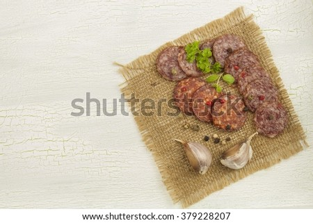 Different kinds of spicy salami on cracked shadowed background.  Preparing home celebrations. Refreshments for a visit. Production of sausages. - stock photo