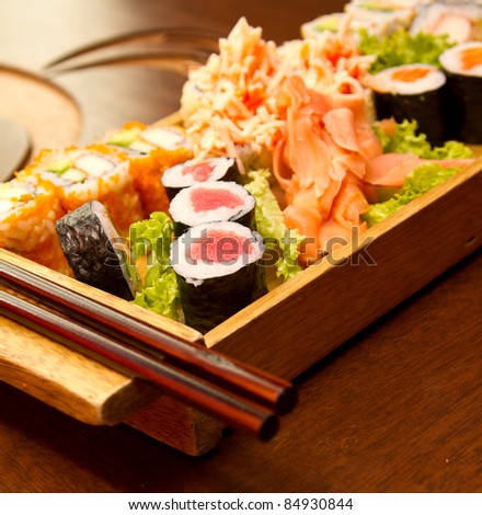Different kinds of sushi on a wood plate - stock photo