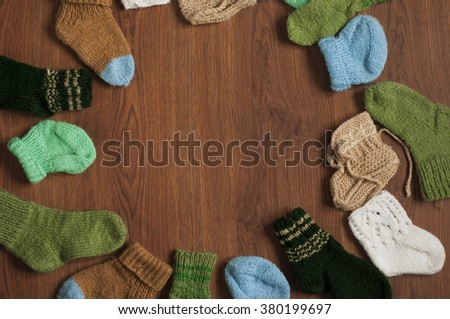 Different  knitted socks for baby with free space for text on wooden background. Flat lay - stock photo
