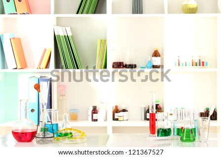 Different laboratory glassware with color liquid on laboratory background - stock photo