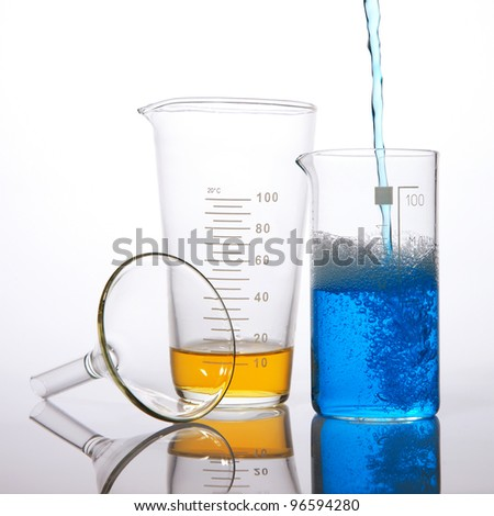 Different laboratory glassware with colored liquid and with reflection - stock photo