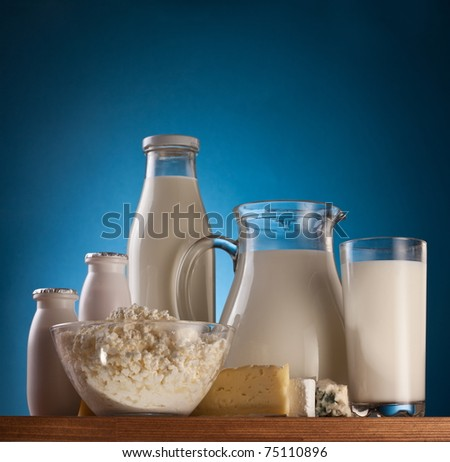 Different milk products: cheese, cream, milk, yoghurt. On a blue background. - stock photo