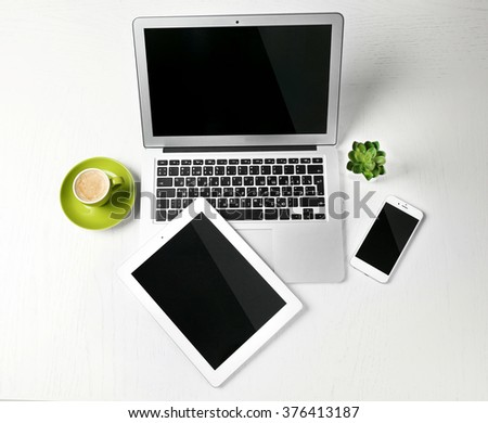 Different modern devices with green plant and cup of coffee on light table - stock photo