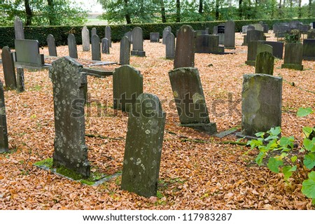 Different old tombstones on a graveyard in the autumn - stock photo