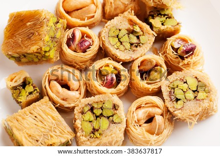Different oriental sweets on a white plate top view, macro - stock photo