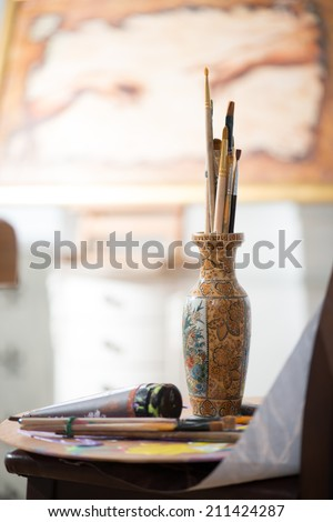 Different paintbrushes standing in one pot on the table moist colors. The picture of painter on background - stock photo