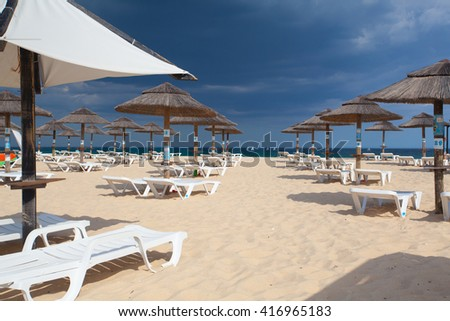 Different parasols and sun loungers on the beach on Tavira island before heavy storm,Algarve. Portugal - stock photo
