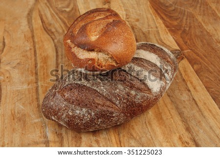 different rye and white flour french bread loaf with on light wooden table background - stock photo