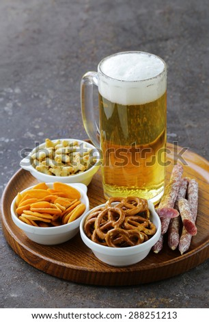 different salted snacks and a glass of fresh beer, rustic still life - stock photo