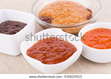 Different sauces in saucers on beige cloth background. - stock photo