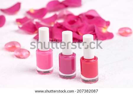 Different shades of rose nail polish on white towel decorated with rose petals - stock photo