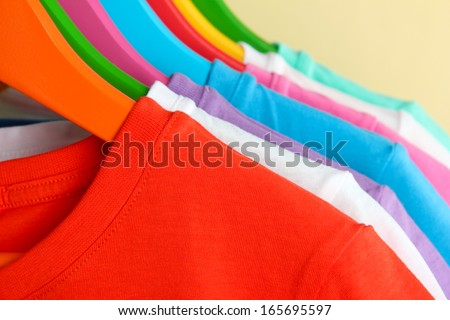 Different shirts on colorful hangers on beige background - stock photo