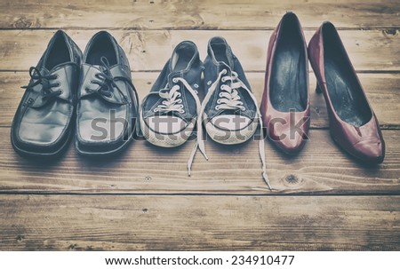Different shoes on a wooden table - stock photo