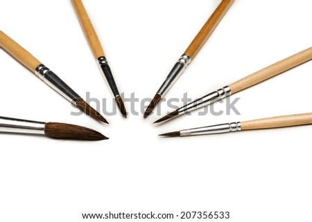 different size artist paint brushes on white - stock photo