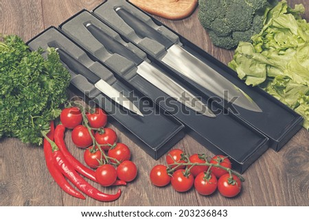 Different size knives and vegetables - stock photo