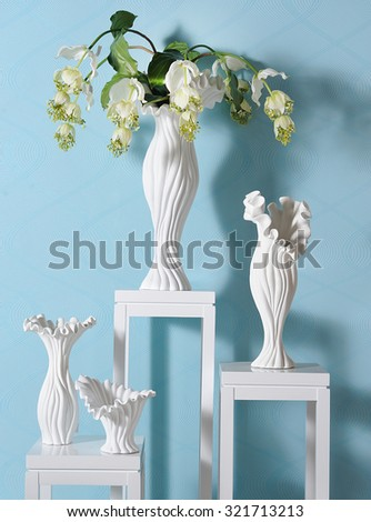 different size vases in a spot of a showroom with beautiful shadows in a blue wall - stock photo