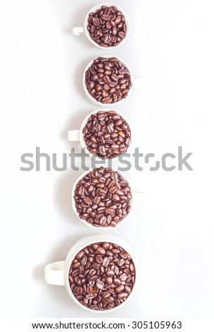Different sized cups full of coffee beans - stock photo