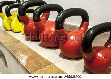 Different sizes of kettlebells weights lying on gym floor - stock photo