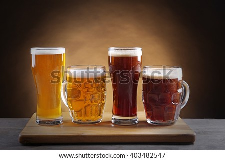 Different sorts of draft beer in glasses on wooden table - stock photo