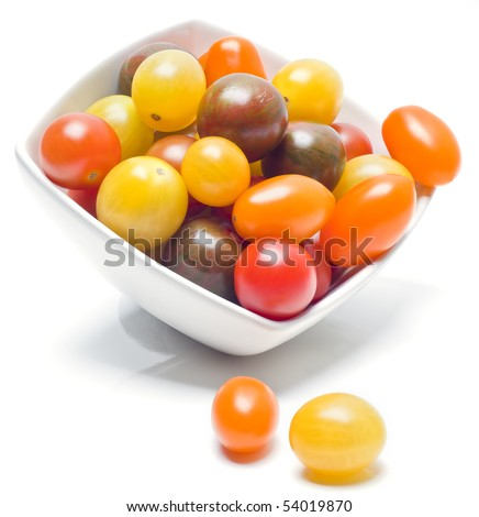 Different sorts of tomatoes served on a white dish, with white background. - stock photo