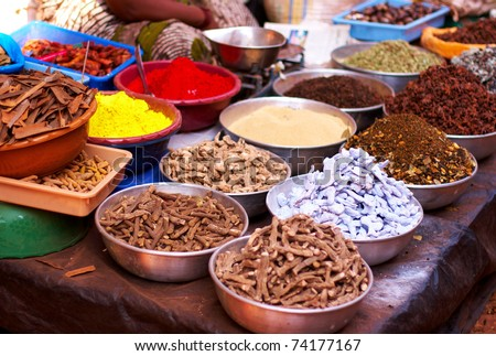 Different spices and herbs in metal bowls on a street market in India - stock photo