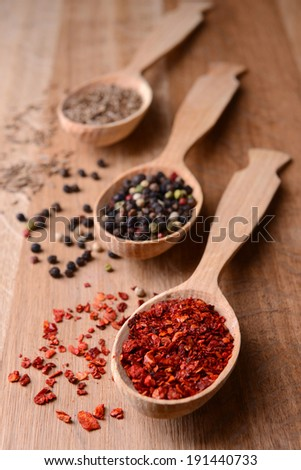 Different spices in spoons on wooden background - stock photo