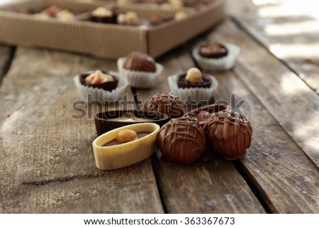 Different tasty chocolate candies on wooden table, close up - stock photo