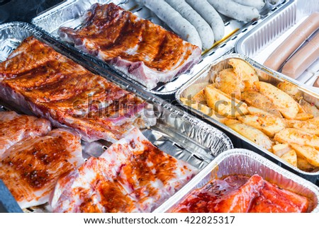 Different tasty grilled meat and sausages on a grill - stock photo
