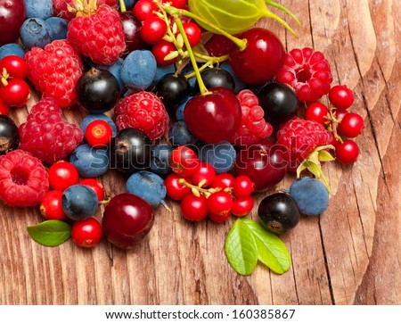 Different type of wild berry fruits on wooden background. - stock photo
