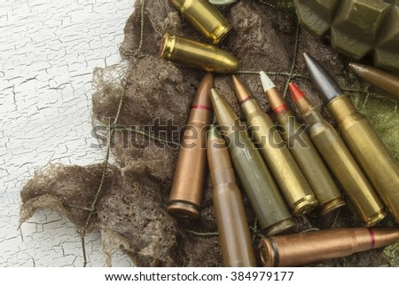 Different types of ammunition on a camouflage background. Preparing for war. Possession of weapons. - stock photo