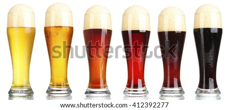 Different types of beer in glasses, isolated on white - stock photo