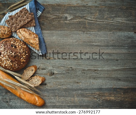 Different types of bread on a wooden background - stock photo